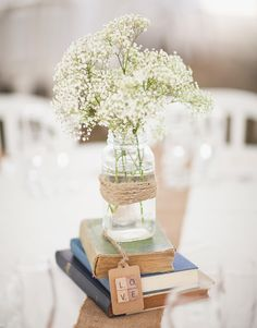 THIS. THISTHISTHISTHISTHIS. This wins the centerpiece war. Only with a single sunflower instead of baby's breath. But totally in a vintage jar stacked on old books.