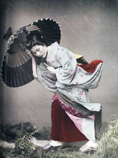 A beautiful hand-tinted 19th century studio photograph of a geisha. The negative was scratched to give the appearance of rain, and the woman's kimono was pinned to the studio backdrop to give an illusion of wind. From: Photography in Japan, 1853-1912