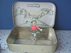 Ice skating rink from old mints tin.  Ice skater is attached to a paper clip.  Now all you need is a magnet to make the skater move.