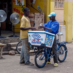 A man buys fan milk from a vendor on the roadside, Lomé, Togo. ©Anders K. West African Countries, Ghana, Milk, Study, Culture, Street, Business, People, Travel