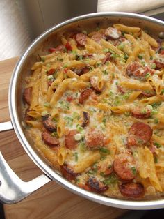 Spicy Sausage Pasta ................ 1 tablespoon olive oil 1 lb smoked sausage 1 1/2 cups diced onion 2 cloves garlic, minced 2 1/4 cups chicken stock 1 can ro-tel 3/4 cup heavy cream 16 oz penne pasta salt, to taste pepper, to taste 2 cups monterey jack cheese, shredded 1/3 cup scallions, thinly sliced