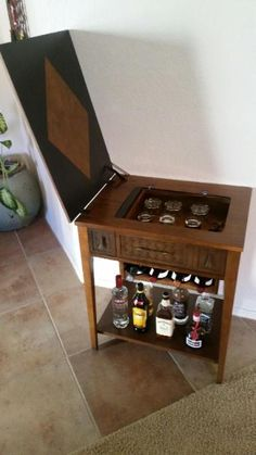 Sewing machine cabinet repurposed as a bar.