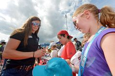 Danica Patrick driver of the Nature's Bakery Chevrolet signs an autograph prior to the NASCAR Sprint Cup Series Quaker State 400 at Kentucky Speedway...