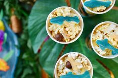 I created an easy Moana snack mix for the party by combining popcorn, coconut chips, Whoppers (coconuts), and blue gummy sharks.