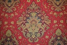 Waverly drapery fabric Far & Away Garnet. The fabric is mostly red with a medallion pattern that has gold and green tones. Heavy enough for light upholstery or can be used for draperies, pillows or bedding.