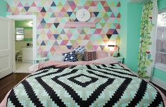 Without using a plan or stencil, the couple painted this mural in their master bedroom. After picking out 11 colors, they painted five or six triangles per night until they'd covered the wall.