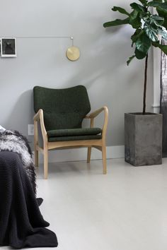 A comfortable lounge chair in deep green, which pairs perfectly with shades of grey and layered textiles.
