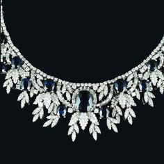 A sapphire and diamond necklace,  designed at the front as an articulated bib of stylised foliate motifs set with brilliant, single and baguette-cut diamonds and cushion-shaped sapphires, the largest at the centre, length 41.0cm.