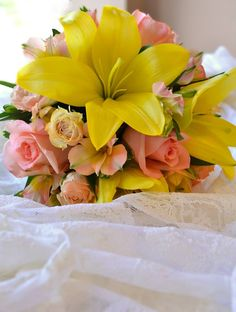 Yellow lily, peach roses and alstroemeria.