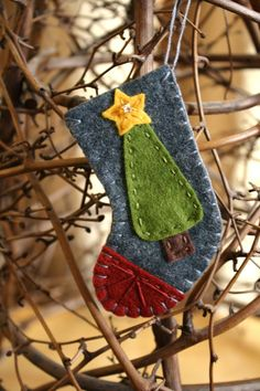 The stocking is make of felt and appliqued and hand embroidered with bead details on the star. The entire stocking measures 3.75 inches in length. The opening at the top is 1.75 inches wide.