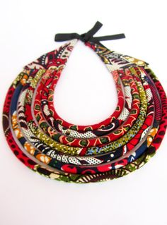 This is a special Red AfricanTribal necklace that is made of African wax print fabric. Hand sewn and assembled by me. The cords are sewn and fitted around acrylic fiber. This awesome African Tribal inspired, trendy color necklace , worn on dressy or casual clothes will definitely be noticed. Length from one end to the other in a straight line is 24 inches (inner circumference). Please let me know if you want changes on the length.  This necklace is ready ship and arrive gift wrapped.  Care…