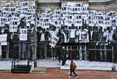 French photographer and street activist JR, was recently in Washington, D.C. working on a mural for his Unframed Project where he takes archived images and uses them in a different context. For this particular piece, he brings to light a photo from Ernest Withers taken during the 1968 Memphis sanitation workers strike and pasted it up on the corner of 14th Street and T streets in Washington where the riots exploded right after Martin Luther King was assassinated in Memphis.