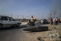 パレスチナ自治区ガザ地区(Gaza Strip)中部デイル・アルバラ(Deir al-Balah)の路上で、イスラエル軍の不発弾を見る通行人(2014年8月1日撮影)。(c)AFP/MARCO LONGARI ▼1Aug2014AFP|ガザ「停戦終了」、発効からわずか数時間 南部で27人死亡 http://www.afpbb.com/articles/-/3022109