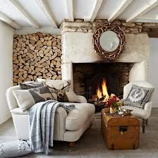 stacked logs, open fire, cream sofas, grey throws and scatter cushions.
