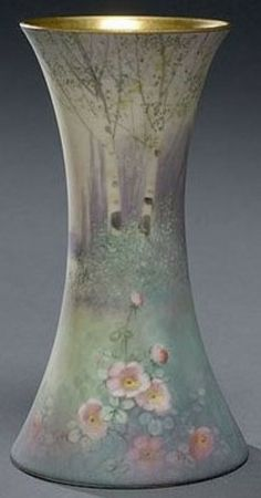 A Pickard Vellum glaze vase, signed E. Challinor, circa 1895 to 1898, waisted cylindrical form with decoration of blooming wild roses and budding trees along a lake, gilt rim.