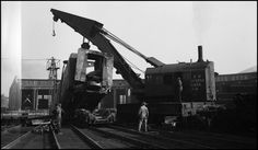 """Opps, tender of NP 5126 being lifted out of Turntable pit at Missoula roundhouse by NP Wrecker 44""  Date: June 22, 1942       Location: Missoula, MT       Photographer: Ron V. Nixon  Railroad: Northern Pacific Railway       Station: Missoula --- USA"