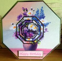 This is a pastel pink and lilac silver edged hexagon shaped birthday card with a vase of pink,lilac,blue and daisies which is layered in . It has silver edged hexagonal tiled pyramage in the center and the back of the card is pink with pink floral outlines and a small matching tile. It is blank inside and comes with an envelope and in a clear bag.I can add a name etc if you wish.