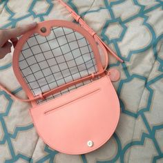 "Kate Spade Saturday Crossbody Kate Spade Half Circle crossbody purse in a light peach salmon color. 100% leather. Black & white grid windowpane interior which shows no sign of wear. Exterior is in good pre-loved condition with minor signs of wear (minor marks and some creases in the strap). Magnetic snap closure. Long adjustable strap. One interior pocket, one exterior slit pocket which is revealed when the flap is opened. 9""x7""x1.5"".  A pretty preppy staple to your wardrobe (: Additional…"
