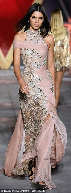 Elegant: Kendall Jenner, meanwhile, sported multiple looks on the runway first stepping out in a pastel pink ethereal floor-length gown that gathered in a number of layers at her feet before falling out into a pleated train