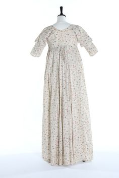 back of A block printed woven muslin open-robe, circa 1800. with fine trellis weave printed in blue, red and brown with delicate floral trails, empire-line bodice with linen inner panels and lining, bust approx 81cm, 32in Provenance: The late Harry Matthews collection..