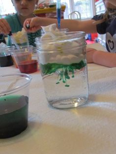 "learn about clouds and weather science experiment- jar, water, shaving cream and food coloring. see how clouds fill up with moisture (food coloring) and then release the ""rain"" below."