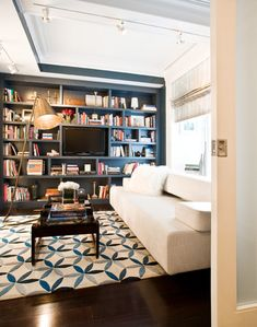Modern Declaration: Chic white & blue media room with white soda, white & blue interlocking circles rug, ...