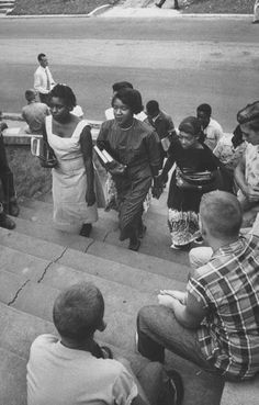 Seven African American teens walking the steps to a school, while the white students are watching on during the demonstration regarding school integration. 1956.