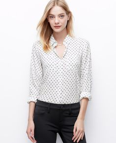 This prettily patterned button-down flaunts a delicate bow motif for an always pulled together look. Point collar. Long sleeves with button closure. Button front. Patch chest pockets. Back yoke with box pleat. Shirttail hem.