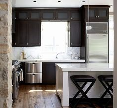 modern kitchen with stone walls, white island and dark cabinets...this may be my favorite kitchen ever!