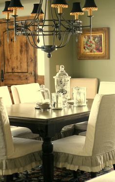 Love the slipcovers oh yeah, great slipcovers, green wall, dark table, black lampshades.