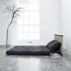 Futon bed for guest room in middle of floor with headboard/pillows.