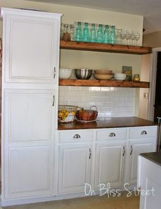 white cabinets with floating shelves and aqua bottles.