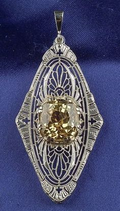 Art Deco Natural Yellow Sapphire Pendant, centering a cushion-cut sapphire measuring approx. 11.04 x 9.93 x 9.15 mm, 14kt white gold Art Deco mount. by aileen