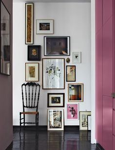 the entrance of apartment with black tiles, pink door, black chair,  white wall with a lot of photos in frame