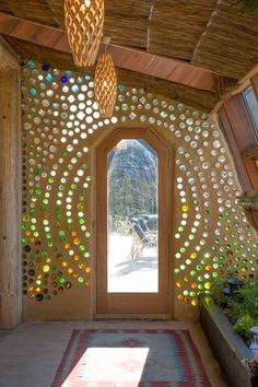 Cool bottle wall in an Airbnb earthship - Grand Designs Earthship Te Timatanga - Earth houses for Rent in Hikuai Maison Earthship, Earth Bag Homes, Colored Glass Bottles, Coloured Glass, Bottle Wall, Bottle House, Natural Building, Green Building, Cob Building