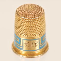 A Fabergé gold and champlevé enamel thimble, workmaster Feodor Afanasiev, Saint Petersburg, circa 1895, with original scratched inventory number 23993. Of traditional form, the upper half and top with hand-dimpled surface, the lower half with with a Greek key design in turquoise blue champleve reserving a rectangular cartouche engraved with initials.
