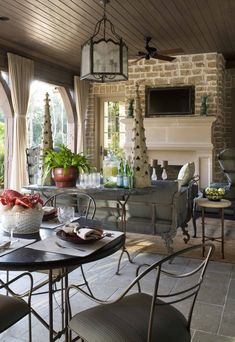 Outdoor room arranged like indoor spaces with an eating/gaming table and a seating area around the fireplace.