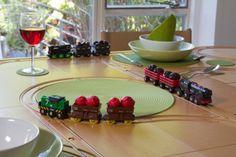 Trens de brinquedo transportam a sobremesa por trilhos desenhados em mesa de jantar