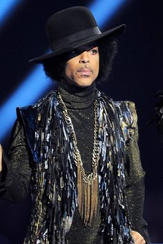 Pin for Later: Look Back at 14 of Prince's Most Legendary Beauty Looks 2014 Prince presented a Brit Award with his hair tucked under a jauntily placed hat.