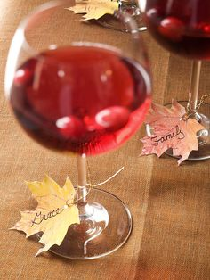 """place cards - Print out our free leaf-shape pattern onto fall-color papers, cut out, and punch a hole at the base of each leaf. Ask guests to pick a leaf and write a word or short phrase describing something they're thankful for, such as """"family"""" or """"good health."""" Attach leaves to the wineglass stems using lengths of gold cord or raffia."""