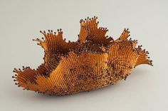 Organic basketry sculpture in copper wire.
