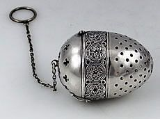 George W. Shiebler and Co. antique sterling egg shape tea ball (tea infuser) with x-shape piercings on upper section and elaborately engraved band separating the sections, c. 1880-1900, silver, USA