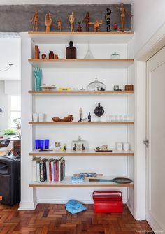 Prateleiras de madeira revestidas com fórmica branca servem com cristaleira  e local para guardar coleções.