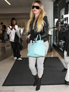 Khloe Kardashian sports fitted sweats and a motorcycle jacket at LAX #dailymail