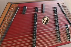 2012 #1605 - A James Jones 3/16/15/8 Custom Hammered Dulcimer, Mahogany frame, Redwood SB made maroon, Lacewood pin panels, Paduak bridges made black.