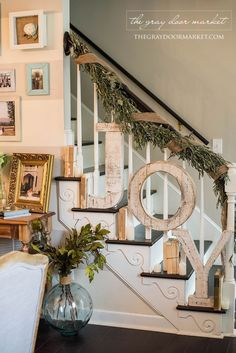 Living Room decor - rustic farmhouse style holiday staircase decor with large letters JOY spelled out and balsam foliage.