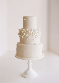A perfectly modern wedding cake is strikingly simple, monochromatic and varying textures.