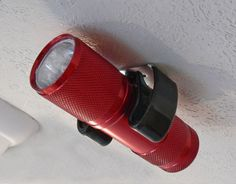 Small LED flashlights are pretty inexpensive nowadays. A good idea is to mount a few of them around the RV for when/if they are needed. To hold it, use a broom clipa perfect fit.)
