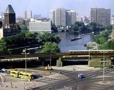 """Willkommen im Jahr 1981, Ost-Berlin, am Ufer der Spree. Die S-Bahn rollt gerade in den S-Bahnhof Jannowitzbrücke ein. Unten links steht ein """"Schlenki"""" an der roten Ampel."""
