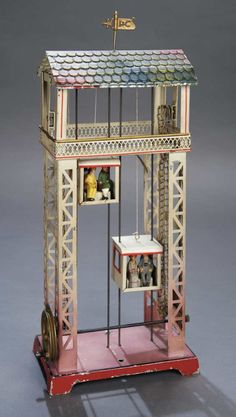 Vintage German Tin Toys, 1910′s - 1920′s.  Swimming Pool with Clock Tower and Pump.  Swimming Pool by Kibri with All-Bisque Dolls.  Mechanical Elevator Tower with Two Spectator Cabins by Doll.  Mechanical Musical Ferris Wheel in Grand Size by Kibri.